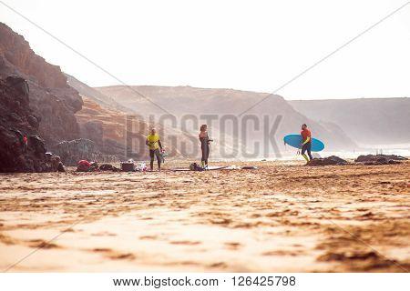 EL COTILLO, FUERTEVENTURA ISLAND, SPAIN - SIRCA JANUARY 2016: Surfers on El Cotillo sandy beach. El Cotillo beach is very popular for surfing on Fuerteventura island