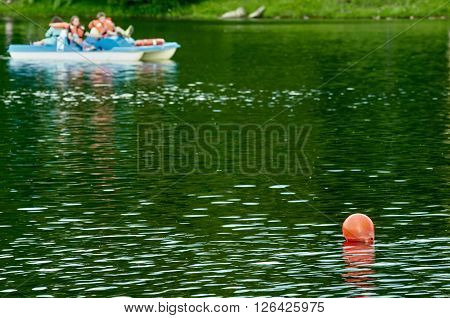 several red buoys on calm lake water, pedal boats in distance