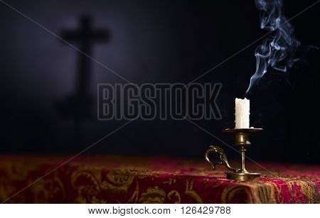 Candle On A Dark Background With The Silhouette Of The Cross