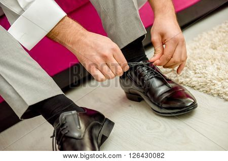 Man tying shoelaces shoes in natural light