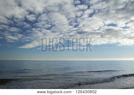 Heaven with stratocumulus clouds over sunset sea