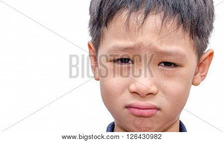 Face of a young asian boy crying