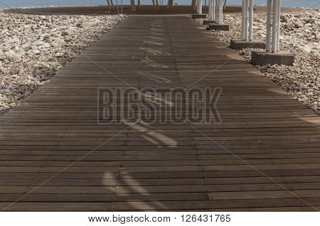 Wooden dock leading to the sea surrounded with natural boulders with heavy shades from parasol