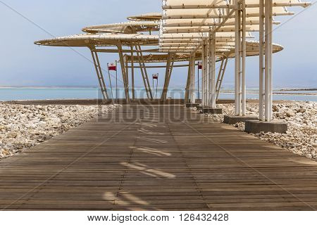 Wooden dock with sunshade leading to the sea surrounded with natural boulders with heavy shades from parasol