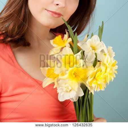 Beautiful woman with flowers on blue background