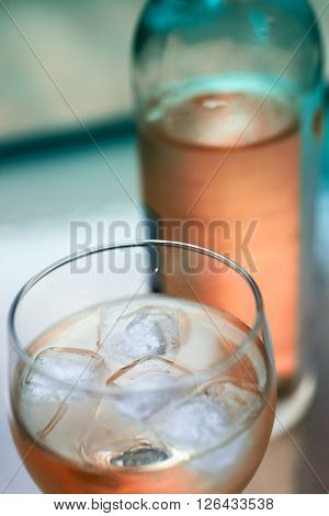 Glass of cold wine with ice on table in color