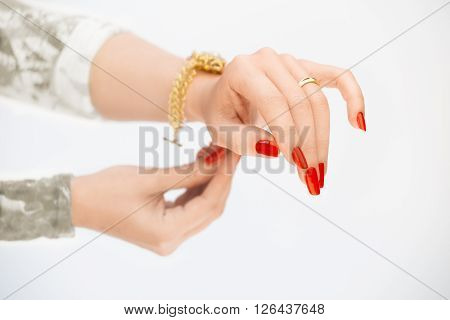 Woman's hands with rings and yellow bracelet on a white background