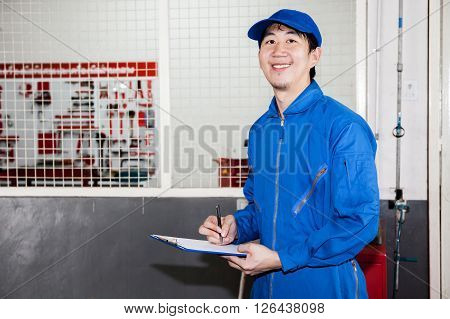 Asian Car Technician Smiling In Garage Service