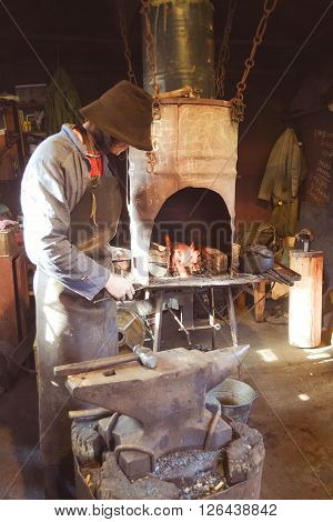 Man blacksmith in the smithy with filter