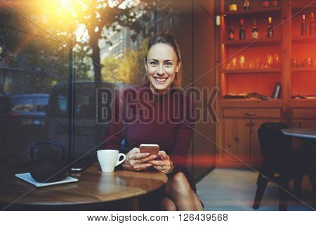 Young woman with beautiful smile posing while sitting with smart phone in modern coffee shop interior gorgeous cheerful female chatting with her friends via cell telephone during rest in cozy cafe
