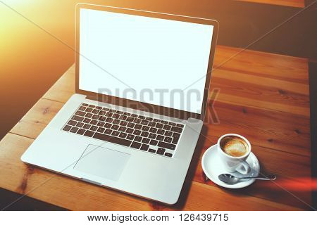 Portable laptop computer and cup of coffee lying on a wooden table in cafe bar interior open net-book with copy space screen for your advertising content or text message remote work via internet