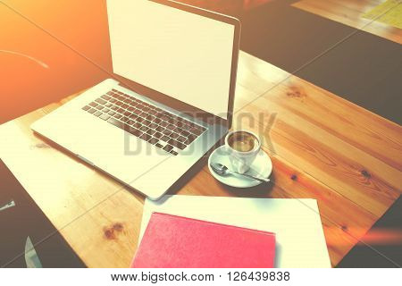 Laptop computer with copy space screen for your text message or information content open net-book and cup of cappuccino lying with notepad on a wooden table in coffee shop remote job via internet