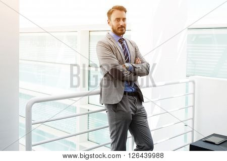 Man confident leader dressed in luxury suit is standing with crossed arms in hallway company there he work. Successful male boss in formal wear is resting after meeting with international partners