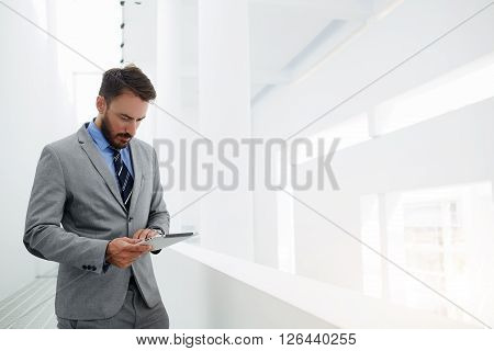 Man banker is searching information in the financial market via digital tablet while is standing in hallway company near copy space. Serious male CEO is reading resume specialists before interview