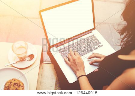 Closeup of woman's hands typing text on laptop computer keyboard during coffee break young female designer is using net-book with mock up blank copy space screen for text message or advertise concept
