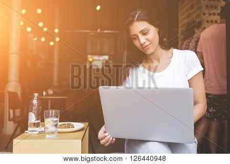 Portrait of a charming latin woman having video call conference on her net-book during lunch break in modern coffee shop. Young female student using laptop computer for learning while sitting in cafe