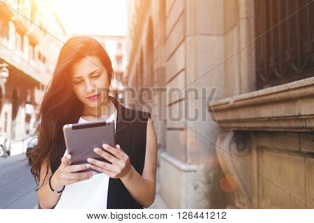 Beautiful woman is reading text message on touch pad while is standing on the street in spring day stylish hipster girl tourist is using tablet computer for navigation during walk in the city abroad