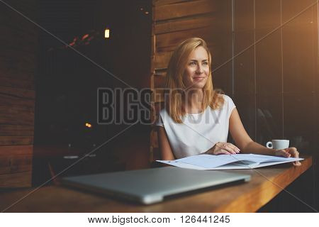 Young beautiful hipster girl with good mood is sitting with big notepad in coffee shop during her recreation time charming Caucasian woman enjoying calm and rest after work on her laptop computer