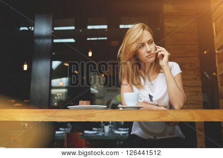 Concerned business woman having unpleasant cell telephone conversation while sitting at the wooden table in coffee shop attractive upset female calling with smart phone during breakfast in cafe