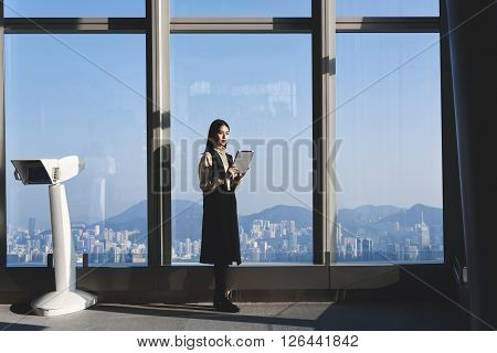 Young Asian hipster girl is holding portable touch pad while is standing in modern interior against window with city view. Businesswoman is searching information in network via digital tablet