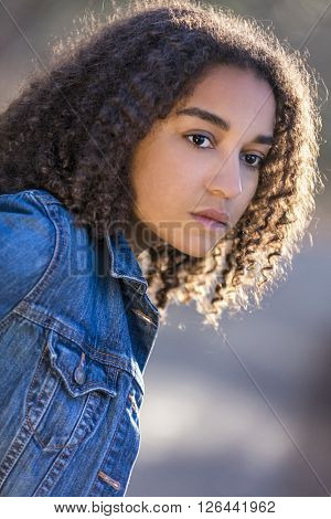 Beautiful mixed race African American girl teenager female young woman outside looking sad depressed or thoughtful
