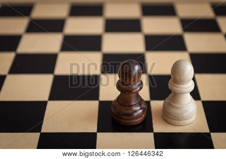 two black and white pawns on a wooden chess Board