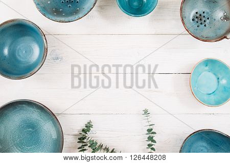 Many turquoise clay empty plates and free space in center on a white wooden background. Flat lay of set of trendy handmade empty plates. Organic food, healthy life, pottery, decoration concept