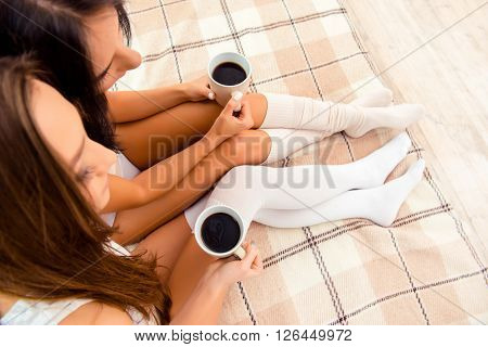 Top View Photo Of Two Cheerful Girls Holding Cups Of Coffee