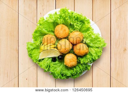 Catering and restaurant food - cheese balls, hot vegetarian snack with olives and lemon closeup. Flat lay, top view. Deep fried cheese balls at lettuce. Festive, banquet meal at wood.