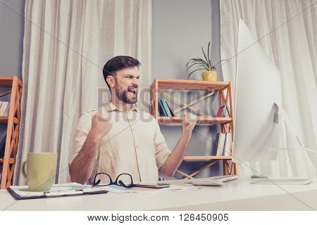 Portrait Of  Happy Young  Businessman Triumphing And Showing Fists