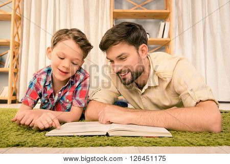 Father And His Little Son Lying On Carpet And Reading Books