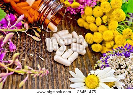 Capsules in brown jar open and on table, fresh flowers fireweed, tansy, chamomile, clover, yarrow, meadowsweet, mint leaves on dark wooden board