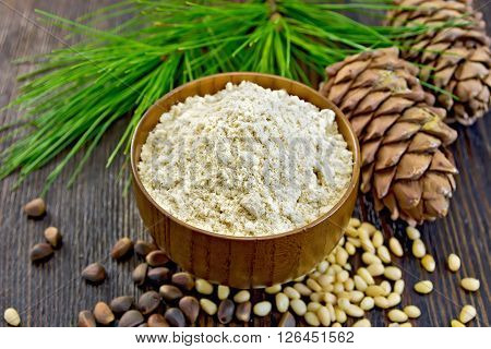 Flour cedar in a wooden bowl, cedar nuts and  two cones, cedar branch with green needles on the background of dark wood planks