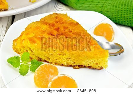 Piece of tart  with mandarin, mint, tangerine slices and spoon in white plate, a towel on the background light wooden boards