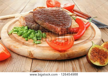 savory : grilled juicy beef pork steak served with hot cayenne peppers green stuff sweet figs and cutlery on wood plate over wooden table