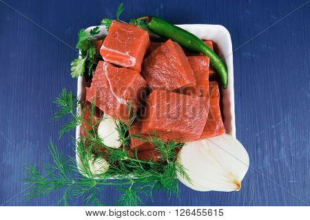 slices of raw fresh beef meat fillet in a white bowls with dill and green peppers serving over blue wooden table
