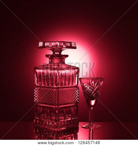 Crystal decanter and wine glass on a red background.
