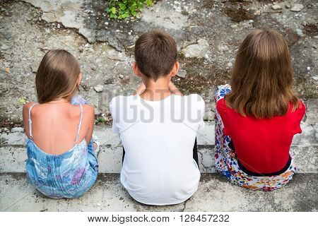 Three teenagers sit with their back. One boy and two girls.