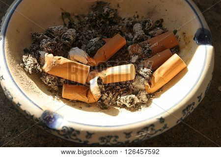 cigarette butts in a white and blue ashtray
