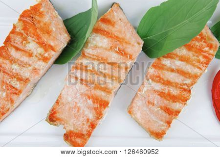 roasted salmon pieces with pepper and lemon on basil leaf over ceramic plate isolated on white background