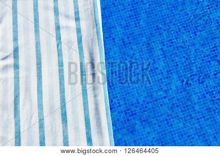 resort background with striped towel  near pool  clear water