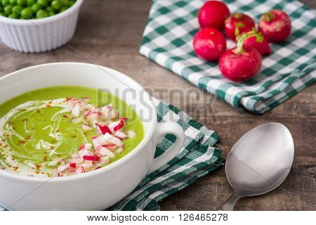 Peas cream with radishes on rustic wooden table