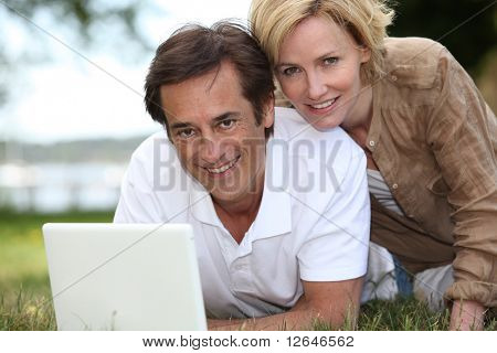 Man and woman laid in the grass in front of a laptop computer