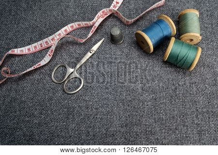 Sewing supplies on the grey fabric background