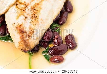 Delicious baked dorado fillet with chard and beans. Macro. Phoro can be used as a whole background.