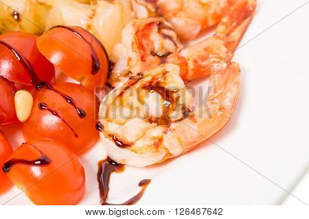 Jumbo shrimp salad with tomatoes topped with pine nuts and parmesan cheese. Macro. Photo can be used as a whole background.