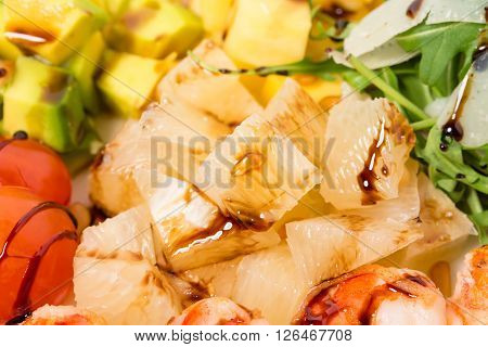 Jumbo shrimp salad with avocado and mango topped with pine nuts and parmesan cheese. Macro. Photo can be used as a whole background.
