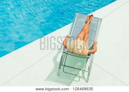 Top view of a girl in the swimming pool on a sun lounger