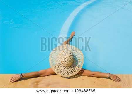 Pretty woman in a hat enjoying a swimming pool at the resort