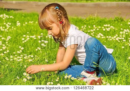 Little sad girl sitting on the lawn among the daisies